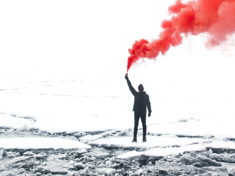 man-with-red-smoke-in-snow